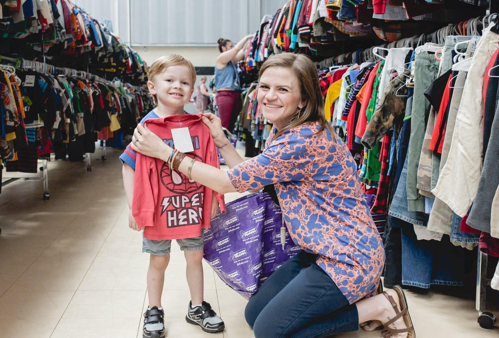 A mom with a large JBF shopping bag on her shoulder stands beside her husband who wears their toddler at a JBF sale.